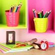 Colorful pencils in pails on shelves on beige background — Stock Photo