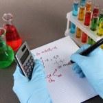 Hand scientist writing formulas — Stock Photo #24023571