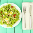 Caesar salad on white plate, on color wooden background — Stock Photo