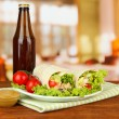 Kebab - grilled meat and vegetables, on plate, on wooden table, on bright background - Stock fotografie