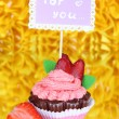 Beautiful strawberry cupcake with postcard on decorative yellow background - Stock Photo