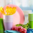 Multicolored plastic tableware on table with tulips close up — Stock Photo #24025495