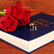 Wedding rings on bible with roses on wooden background — Stock Photo #24025707