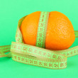 Orange with measuring tape, on color background - Lizenzfreies Foto