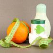 Orange with measuring tape and body cream, on color background - Stock Photo