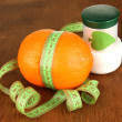 Orange with measuring tape and body cream, on wooden background - Lizenzfreies Foto