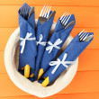 Forks and knives wrapped in blue paper napkins, in basket,  on color wooden background - Stock fotografie