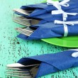 Forks and knives wrapped in blue paper napkins, on color wooden background - Stock fotografie
