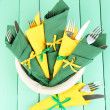 Forks and knives wrapped in green and yellow paper napkins, on color wooden background - Stock fotografie