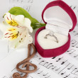 Treble clef, flower and box holding wedding ring on musical background — ストック写真