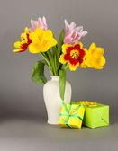Gri arka plan üzerinde hediyeler ile kova güzel laleler — Stok fotoğraf