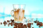 Cold coffee with ice in glass on blue background — Stock Photo