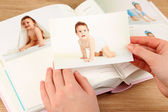 Photos in hands and photo album on wooden table — Stock Photo