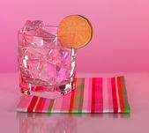 Ice in a glass on a color background — Stock Photo