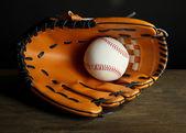Beysbol eldiveni ve koyu arka plan üzerinde topu — Stok fotoğraf