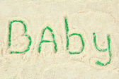 Word baby making with powdered milk on green background — Stock Photo