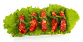 Salami rolls on green salad leaves, on white plate, isolated on white — Stock Photo