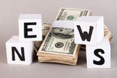 """White paper cubes labeled """"News"""" with money on grey background — 图库照片"""