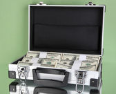 Suitcase with 100 dollar bills on green background — Stock Photo