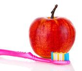 Apple con uno spazzolino da denti isolato su bianco — Foto Stock