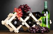 ワインのボトルは灰色の背景上の木製のスタンドに配置 — ストック写真
