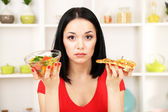 Pretty girl selects pizza or diet on kitchen background — Stock Photo