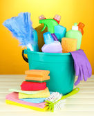 Cleaning items in bucket on color background — Stock Photo