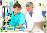 Physician and assayer during research on room background — Stock Photo