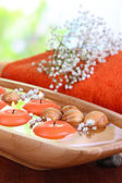 Beautiful candles in water on wooden table on natural background — Stock Photo