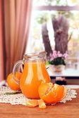 полный кувшин мандариновый сок, на деревянный стол на светлом фоне — Стоковое фото
