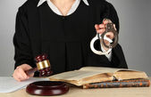 Judge sitting at table during court hearings on grey background — Stock Photo