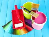 Boyama için ayarla: boya kapları, fırçalar, mavi ahşap masa üzerinde rulo — Stok fotoğraf