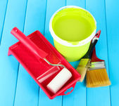Set for painting: paint pot, brushes, paint-roller on blue wooden table — Stock Photo