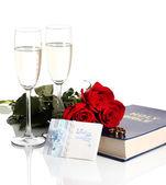 Vigselringar på bibeln med rosor och glas champagne isolerad på vit — Stockfoto
