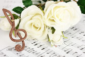 Treble clef and roses on musical background — Stock Photo