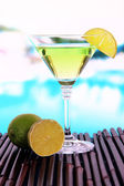 Green cocktail with lime on table on bright background — Stock Photo
