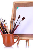 Small easel with sheet of paper and art supplies isolated on white — Stock Photo
