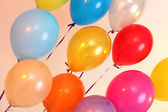 Many bright balloons on orange background — Stock Photo