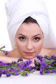 Beautiful young woman with towel on her head and flowers isolated on white — Stock Photo