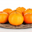 Tasty mandarines on wicker mat isolated on white — Stock Photo
