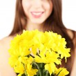Young beautiful girl with nice flowers in her hand, isolated on white - Stock Photo
