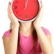 Girl holding clock over face isolated on white — Стоковая фотография