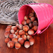Overturned bucket with hazelnuts on wooden background - Stock Photo