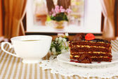 Cup of tea and delicious cake on window background — Stock Photo