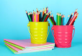 Colorful pencils with copybooks on blue background — Stock Photo