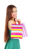 Young beautiful girl in green dress holding bright shopping bags, isolated on white — Stock Photo