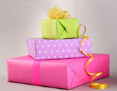 Bright gifts with bows on grey background — Stock Photo