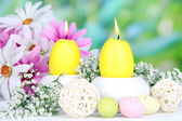 Velas de pascua con flores sobre fondo brillante — Foto de Stock
