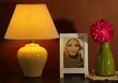 White photo frame and glowing lamp on wooden table on brown wall background — Stock Photo