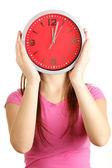 Mädchen halten Uhr übers Gesicht isoliert auf weiss — Stockfoto